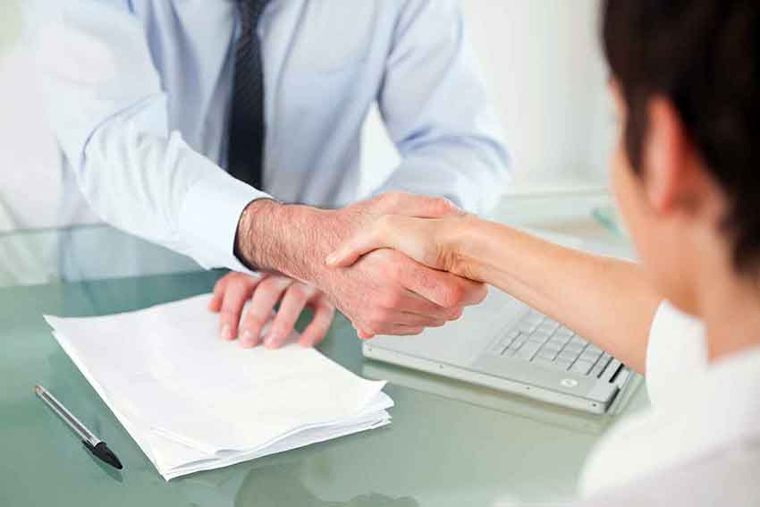 Lawyer shakes client's hand after successful settlement