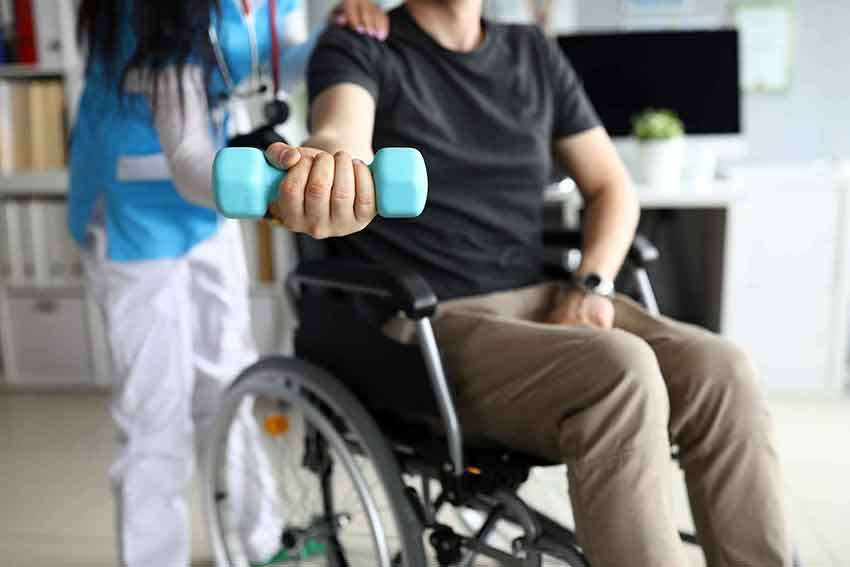 Physical therapist assists man in wheelchair